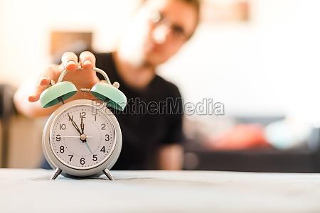 man is pushing an alarm clock