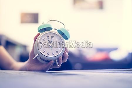 man is holding an alarm clock
