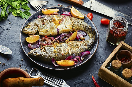 baked trout with lemon on plate