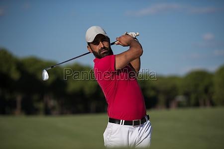 golfer hitting a sand bunker shot
