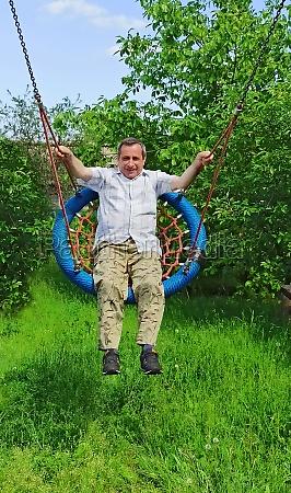 adult man riding on hanging swing