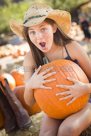 preteen girl holding a large pumpkin