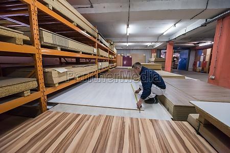 carpenter measuring wooden board