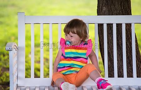 cute little girl sitting on wooden