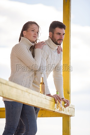 young couple drinking beer together at
