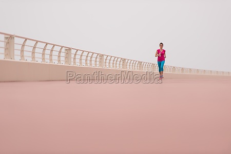 woman busy running on the promenade