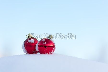 red christmas balls in fresh snow
