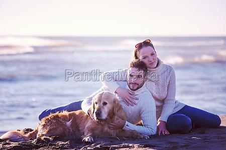 couple with dog enjoying time on