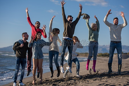 young friends jumping together at autumn