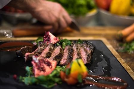 closeup of chef hands serving beef
