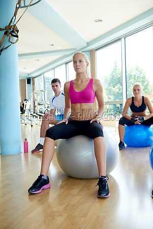 group of people exercise with balls