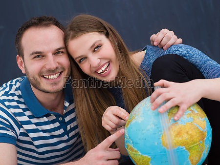 couple in casual clothing investigating globe