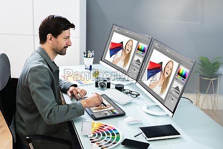 graphic photo designer using computer screen