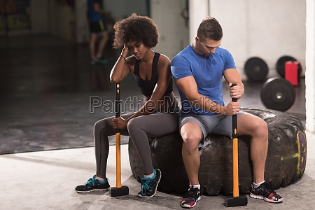 multiethnic couple after workout with hammer