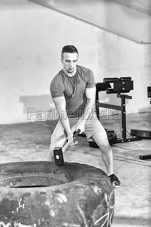 man workout with hammer and tractor