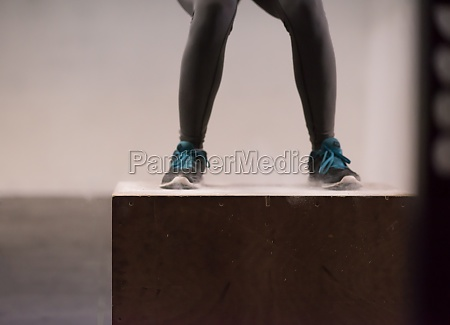 black woman is performing box jumps