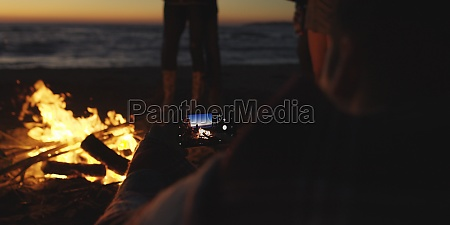 couple taking photos beside campfire on