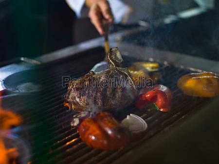 chef cooking steak with vegetables on