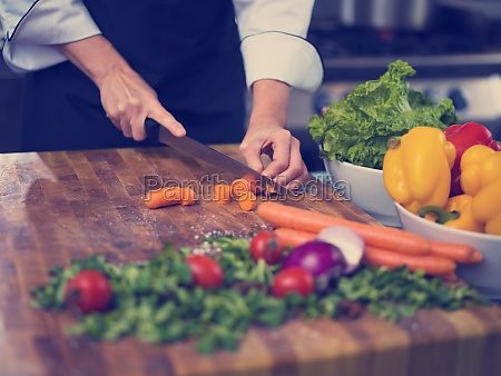 chef hands cutting carrots