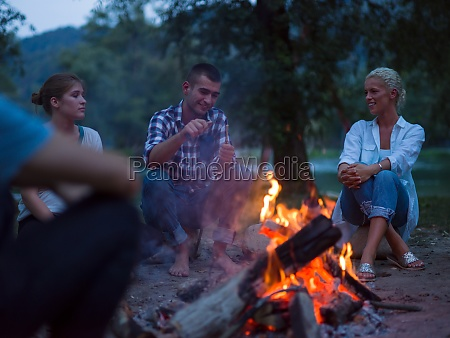 young friends relaxing around campfire