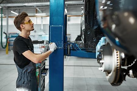 male mechanic lifts the car auto