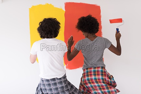 multiethnic couple painting interior wall
