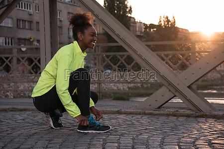 african american woman runner tightening shoe