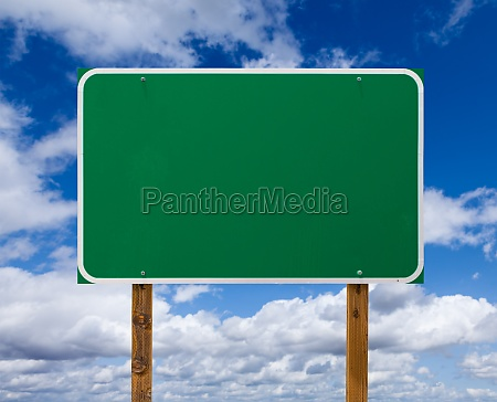 blank green road sign with wooden