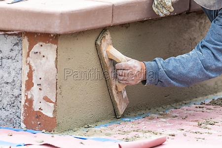 worker smoothing cement with wooden float