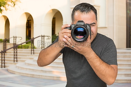 hispanic young male photographer with dslr