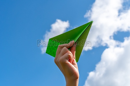 child hand with paper plane against