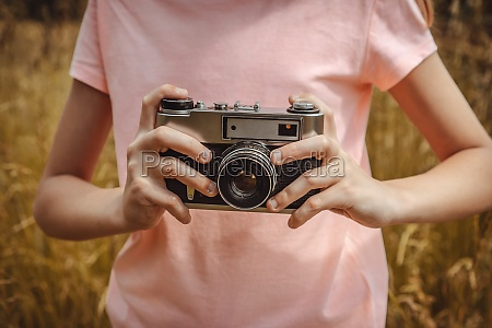 girl taking photo outdoors with old