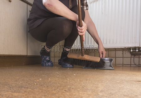 woman with broom cleaning as unpaid