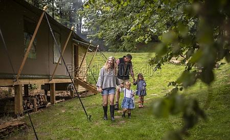 family walking outside cabin in woods