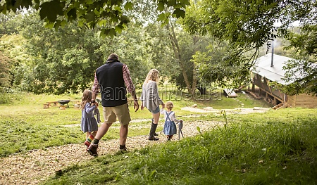 family holding hands walking on path