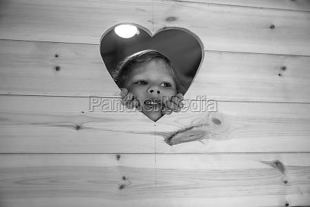 cute girl peering through heart shape