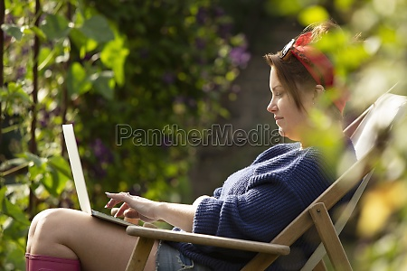 woman using laptop in sunny summer