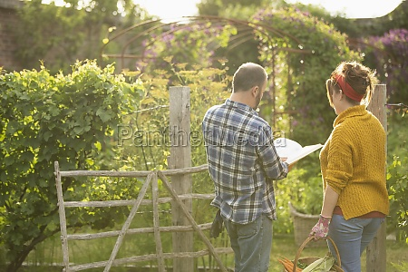couple with book harvesting vegetables in