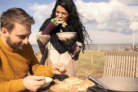 happy couple eating on sunny beach