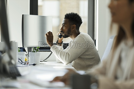 businessman talking on telephone at computer