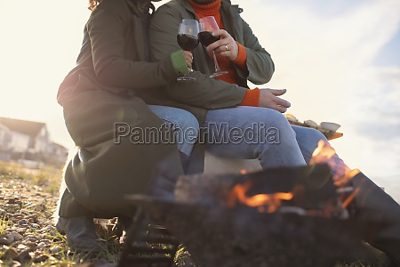 couple in winter coats drinking red