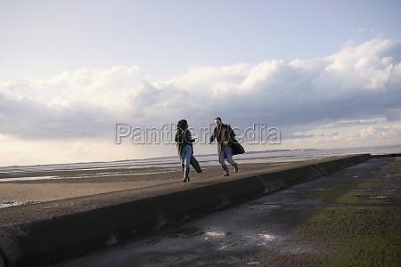 couple running on ocean beach jetty