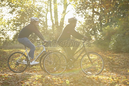 couple bike riding through autumn leaves