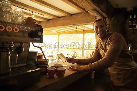 portrait happy male coffee shop owner