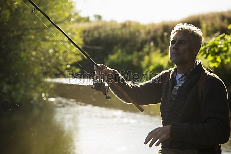 man casting fly fishing pole at