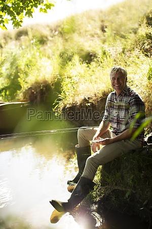portrait happy man fly fishing at