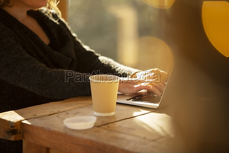 woman with coffee working at laptop