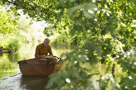 man writing and fishing in boat