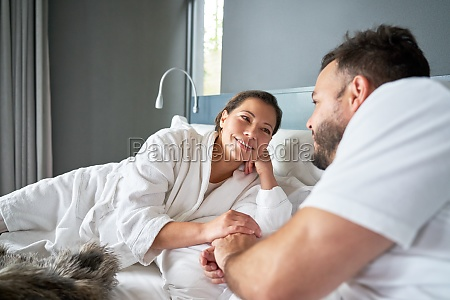 happy affectionate couple relaxing on bed