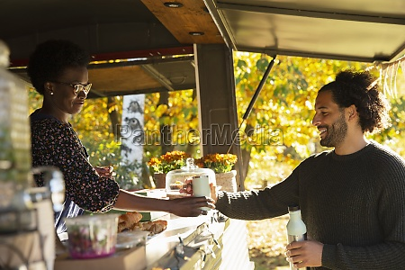 food cart owner serving coffee to